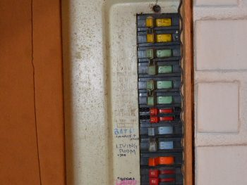 Photo of a Zinsco electrial panel. Half of it is covered up.