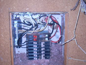 A photo of an electrical panel located in a shop with a rats nest inside of it.